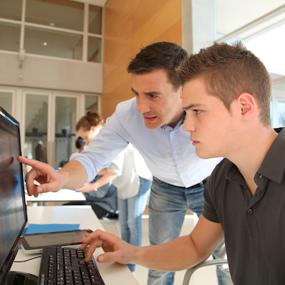 Image of male apprentice working in office - Apprenticeship Employers FAQs